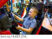 Купить «Мальчик за рулем игрового автомата», фото № 4657216, снято 21 мая 2013 г. (c) Сергей Лаврентьев / Фотобанк Лори