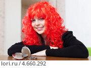 Купить «Женщина в красном парике сидит за столом с зеркалом и расческой», фото № 4660292, снято 21 декабря 2012 г. (c) Яков Филимонов / Фотобанк Лори