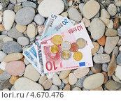 Купюры и монеты евро на морской гальке. Стоковое фото, фотограф Raulin / Фотобанк Лори