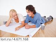 Купить «Молодой человек и его девушка вместе рассматривают карту, лежа на полу», фото № 4671168, снято 14 июля 2011 г. (c) Wavebreak Media / Фотобанк Лори