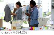 Купить «Fashion designer on the phone while discussing with a colleague», видеоролик № 4684268, снято 9 апреля 2020 г. (c) Wavebreak Media / Фотобанк Лори