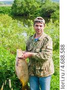 Купить «Радостный рыбак держит в руках большого сазана на фоне реки», эксклюзивное фото № 4688588, снято 31 мая 2013 г. (c) Игорь Низов / Фотобанк Лори