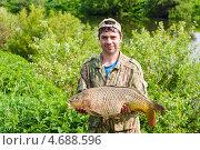 Купить «Радостный рыбак держит в руках пойманного крупного сазана», эксклюзивное фото № 4688596, снято 31 мая 2013 г. (c) Игорь Низов / Фотобанк Лори