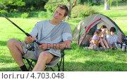 Купить «Smiling man fishing in front of his family», видеоролик № 4703048, снято 17 июля 2019 г. (c) Wavebreak Media / Фотобанк Лори