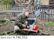 Дачник ремонтирует мотокультиватор на огороде. Стоковое фото, фотограф Елена Бачурина / Фотобанк Лори