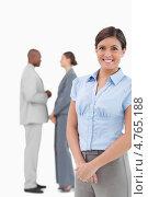 Купить «Счастливая предпринимательница стоит на фоне подчиненных», фото № 4765188, снято 8 ноября 2011 г. (c) Wavebreak Media / Фотобанк Лори