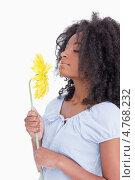 Купить «Молодая афро-американка вдыхает аромат цветка», фото № 4768232, снято 11 ноября 2011 г. (c) Wavebreak Media / Фотобанк Лори
