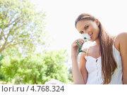 Купить «Привлекательная девушка в парке вдыхает аромат цветов в руках», фото № 4768324, снято 17 ноября 2011 г. (c) Wavebreak Media / Фотобанк Лори