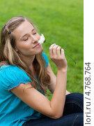 Купить «Девушка держит в руке цветок и вдыхает его аромат», фото № 4768764, снято 14 ноября 2011 г. (c) Wavebreak Media / Фотобанк Лори