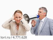 Мужчина кричит в мегафон около уха женщины пытающейся закрыть уши руками. Стоковое фото, агентство Wavebreak Media / Фотобанк Лори