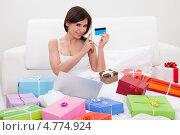 Купить «Виртуальный шопинг. Счастливая девушка с кучей коробок на диване держит банковскую карту», фото № 4774924, снято 19 января 2013 г. (c) Андрей Попов / Фотобанк Лори