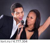 Купить «Красивая темнокожая пара поет в микрофон», фото № 4777304, снято 9 марта 2013 г. (c) Андрей Попов / Фотобанк Лори