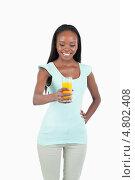 Купить «Улыбающаяся молодая женщина держит стакан апельсинового сока», фото № 4802408, снято 11 октября 2011 г. (c) Wavebreak Media / Фотобанк Лори