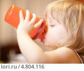Купить «Маленькая девочка пьет из оранжевой специальной чашки», фото № 4804116, снято 5 февраля 2010 г. (c) Станислав Фридкин / Фотобанк Лори