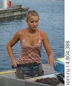 Молодая женщина нарезает с ножом для разделки рыбы на рынке Марселя (2009 год). Редакционное фото, фотограф Александр Элеазер / Фотобанк Лори