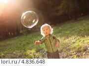 Маленький мальчик на закате ловит мыльные пузыри. Стоковое фото, фотограф Елена Ефимова / Фотобанк Лори