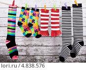 Разноцветные смешные  носки сушатся на веревке на фоне деревянной крашеной стены. Стоковое фото, фотограф Элина Гаревская / Фотобанк Лори