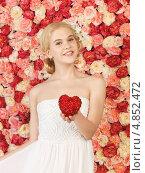Купить «Юная девушка со светлыми волосами с сердцем в руках на фоне цветов», фото № 4852472, снято 2 марта 2013 г. (c) Syda Productions / Фотобанк Лори