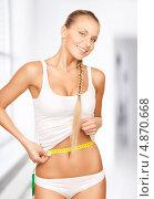 Купить «Красивая стройная девушка с лентой сантиметра в руках измеряет объемы своего тела», фото № 4870668, снято 8 мая 2010 г. (c) Syda Productions / Фотобанк Лори