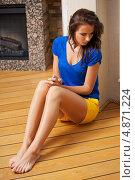 Купить «Задумчивая девушка сидит на деревянном полу», фото № 4871224, снято 21 июля 2012 г. (c) Syda Productions / Фотобанк Лори