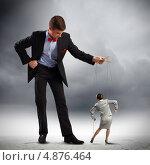 Купить «Бизнесмен-манипулятор заставляет двигаться куклу-марионетку», фото № 4876464, снято 12 января 2013 г. (c) Sergey Nivens / Фотобанк Лори