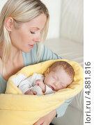 Купить «Мама держит спящего малыша сидя на ковре», фото № 4881816, снято 31 октября 2011 г. (c) Wavebreak Media / Фотобанк Лори
