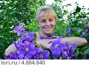 Купить «Портрет женщины средних лет среди цветов клематиса», фото № 4884840, снято 19 июня 2013 г. (c) Ирина Борсученко / Фотобанк Лори