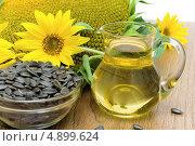 Купить «Подсолнухи, подсолнечное масло и чашка с семечками на столе», фото № 4899624, снято 26 июля 2013 г. (c) Ласточкин Евгений / Фотобанк Лори