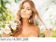 Купить «Красивая молодая женщина с волнистыми волосами на фоне летнего сада с цветами в руках», фото № 4901268, снято 14 августа 2010 г. (c) Syda Productions / Фотобанк Лори