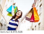 Купить «Счастливая девушка с покупками в пакетах на фоне города», фото № 4915928, снято 29 июня 2013 г. (c) Syda Productions / Фотобанк Лори