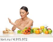 Купить «Красивая молодая женщина отказывается от вредной еды в пользу овощей и фруктов», фото № 4915972, снято 12 января 2013 г. (c) Syda Productions / Фотобанк Лори