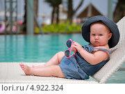 Маленькая девочка сидит в шезлонге у бассейна с бирюзовой водой. Стоковое фото, фотограф Роман Кокорев / Фотобанк Лори