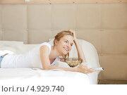 Счастливая девушка смотрит дома телевизор с пультом в руках. Стоковое фото, фотограф Syda Productions / Фотобанк Лори