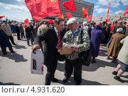 Мужчина в костюме выбирает газеты на митинге коммунистов (2013 год). Редакционное фото, фотограф Даниил Максюков / Фотобанк Лори