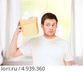 Купить «Молодой мужчина в белой футболке с подарком в коробке», фото № 4939360, снято 6 июня 2013 г. (c) Syda Productions / Фотобанк Лори