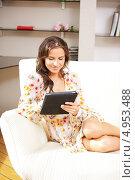 Купить «Счастливая молодая женщина читает с планшетного компьютера дома», фото № 4953488, снято 17 ноября 2018 г. (c) Syda Productions / Фотобанк Лори