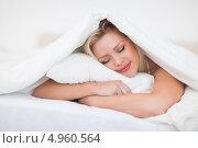 Купить «Привлекательная девушка спит на животе под одеялом, обнимая подушку», фото № 4960564, снято 12 апреля 2012 г. (c) Wavebreak Media / Фотобанк Лори