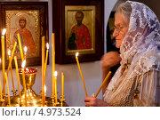Купить «Пожилая женщина ставит свечку около иконостаса в Храме Святого пророка Божия Илии, что в Китай-городе, в  Ильин день 2 августа 2013», фото № 4973524, снято 2 августа 2013 г. (c) Николай Винокуров / Фотобанк Лори