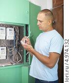 Мужчина переписывает показания счетчиков электрической энергии. Стоковое фото, фотограф Яков Филимонов / Фотобанк Лори