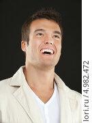Купить «Молодой брюнет смеется и смотрит наверх. Портрет на черном фоне», фото № 4982472, снято 10 ноября 2010 г. (c) BestPhotoStudio / Фотобанк Лори