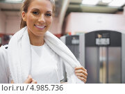 Купить «Улыбающаяся девушка с полотенцем на шее стоит в спортзале», фото № 4985736, снято 20 июня 2012 г. (c) Wavebreak Media / Фотобанк Лори
