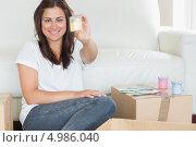 Купить «Молодая женщина держит в руках желтый колер, сидя на ковре среди картонных коробок», фото № 4986040, снято 4 июля 2012 г. (c) Wavebreak Media / Фотобанк Лори