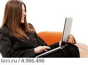 Купить «Деловая девушка сидит в оранжевом кресле с ноутбуком в руках», фото № 4986496, снято 19 июня 2007 г. (c) Syda Productions / Фотобанк Лори