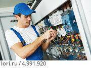 Купить «Электрик. Мужчина в рабочей одежде стоит у щитка», фото № 4991920, снято 21 августа 2013 г. (c) Дмитрий Калиновский / Фотобанк Лори