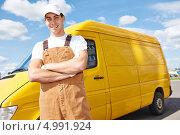 Купить «Доставка. Мужчина в рабочем комбинезоне и кепке стоит на фоне желтого фургона», фото № 4991924, снято 26 августа 2013 г. (c) Дмитрий Калиновский / Фотобанк Лори