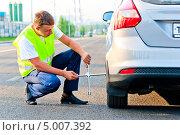 Купить «Механик в светоотражающем жилете откручивает колесо автомобиля на дороге», фото № 5007392, снято 30 июня 2013 г. (c) Константин Лабунский / Фотобанк Лори