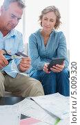 Купить «мужчина в возрасте разрезает пополам кредитную карту жены», фото № 5009320, снято 7 апреля 2013 г. (c) Wavebreak Media / Фотобанк Лори