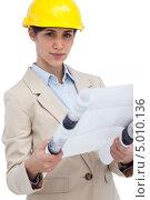 Купить «серьезная деловая девушка в желтой каске держит чертежи в руках», фото № 5010136, снято 29 марта 2013 г. (c) Wavebreak Media / Фотобанк Лори