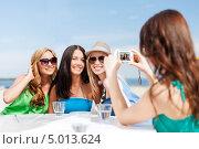 Купить «Счастливые девушки сидят в кафе у моря и фотографируются», фото № 5013624, снято 4 июля 2013 г. (c) Syda Productions / Фотобанк Лори