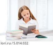 Купить «Маленькая школьница увлеченно читает книжку», фото № 5014032, снято 7 августа 2013 г. (c) Syda Productions / Фотобанк Лори